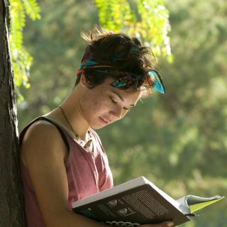 Young woman reads textbook under tree