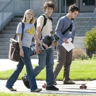 Students walk across campus carrying skateboards