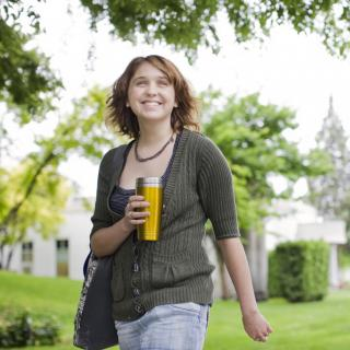 Young woman walking across campus