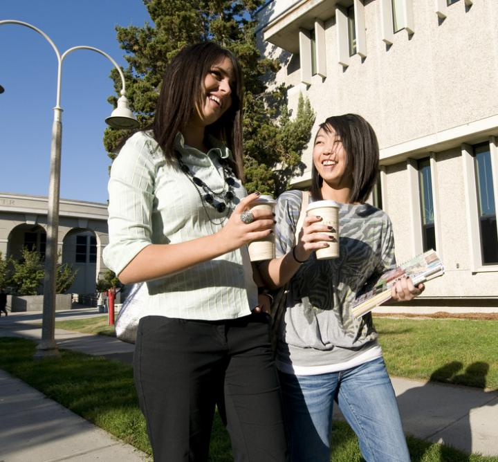 Two young women walking on campus