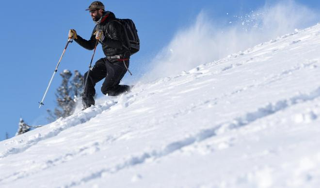 Young man skis down powdery slope