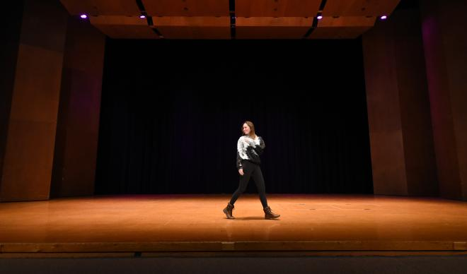 A contestant of the 2017 Miss C of I walks across the Jewett Auditorium stage