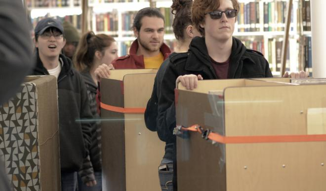 A group of C of I students cart books to new shelves inside the Cruzen-Murray Library