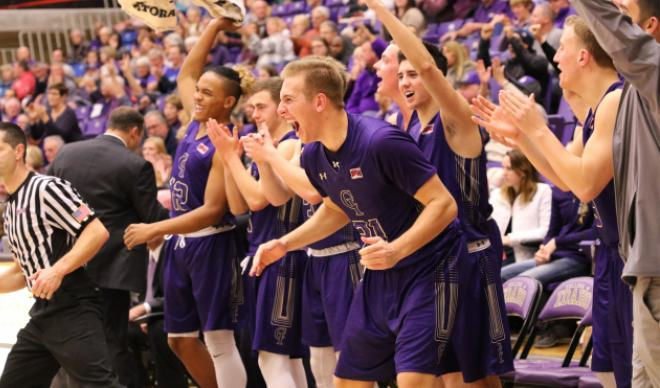 The C of I men's basketball team celebrates on the sidelines.
