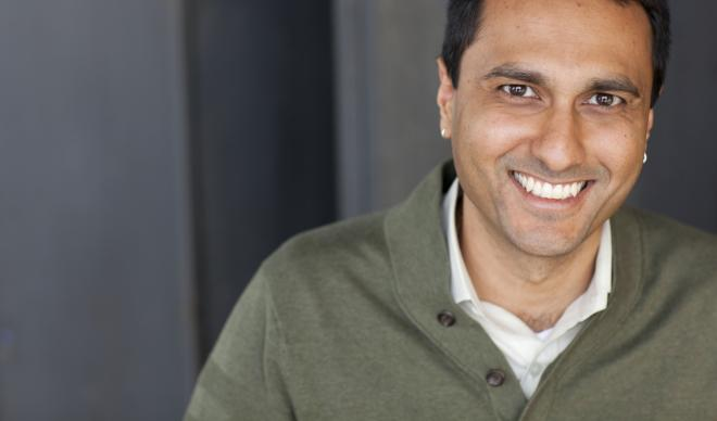 Dr. Eboo Patel smiles for a portrait on a neutral background.