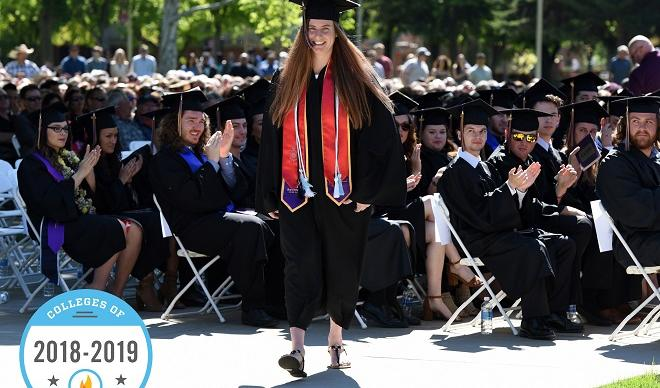 "A C of I student at the 2018 Commencement featuring a 2018-2019 ""Colleges of Distinction"" badge."