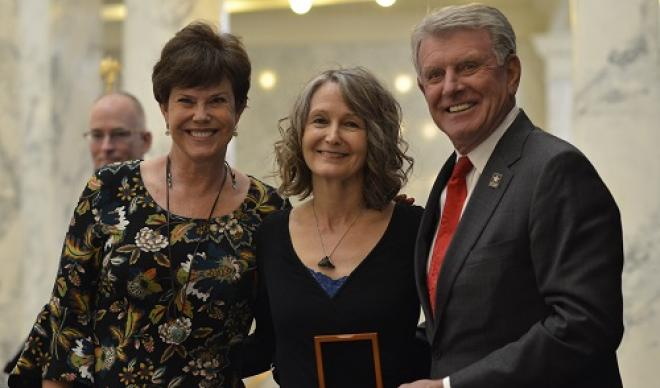 Diane Raptosh (center) receives the Governor's Award for Excellence in the Arts from Lori (left) and Butch Otter (right).