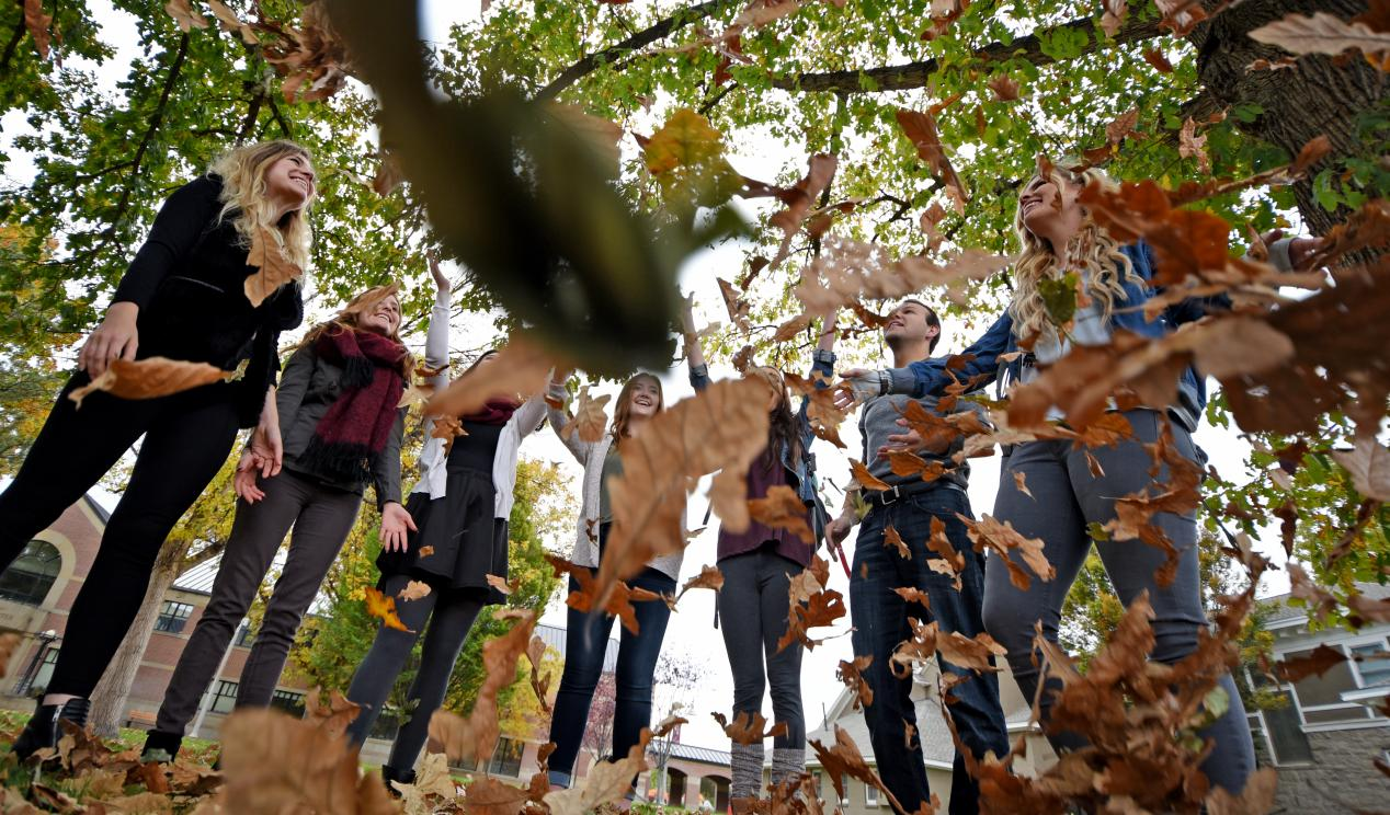 Students throwing leaves in the air