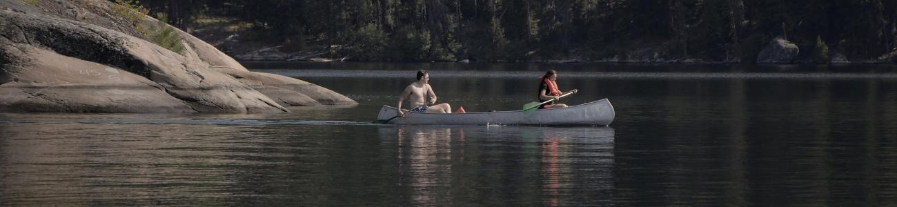 Two students paddle a canoe on a lake