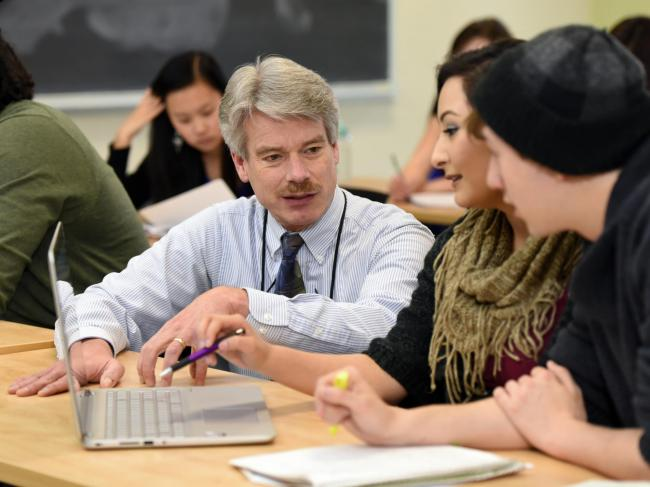 Professor talks to two students looking at laptop